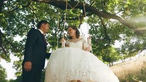 De gelukkige jonge paarbruid en de bruidegom in huwelijk kleden het slingeren op schommeling in park schommeling op tak van een e stock videobeelden