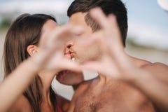 De gelukkige jonge paarkus en maakt een hart door handen Paar dat op het strand loopt Liefde stock afbeeldingen