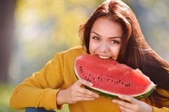De gelukkige jonge plak van de vrouwenbeet van rijpe watermeloen in het park Royalty-vrije Stock Afbeelding