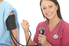 De gelukkige Jonge Professionele Vrouwelijke Druk van Artsentaking the blood van een Patiënt Stock Foto