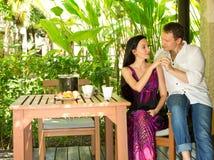 De gelukkige jonge romantische paarzitting bij een lijst en heeft lunch bij openlucht Liefdeverhaal en mensen` s houdingen Mooi h royalty-vrije stock fotografie