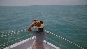 De gelukkige jonge toeristenvrouw houdt haar hoed op de bootneus van het cruisejacht genietend van perfect winderig zonnig overze stock video