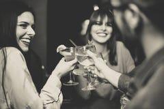 De gelukkige jonge vrienden die en cocktails roosteren toejuichen bij disco versperren - Multiraciale mensen die pret hebben geni stock afbeelding