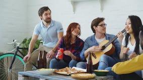 De gelukkige jonge vrienden hebben partij bij gedeelde flat en thuis het zingen samen terwijl hun vriend het spelen gitaar stock footage