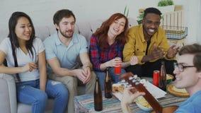 De gelukkige jonge vrienden hebben partij bij gedeelde flat en thuis het zingen samen terwijl hun vriend het spelen gitaar stock video