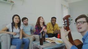 De gelukkige jonge vrienden hebben partij het spelen gitaar en thuis het zingen samen stock videobeelden
