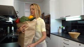 De gelukkige Jonge Vrouw brengt een Zak van Kruidenierswinkels aan de Keuken stock video