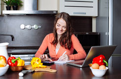 De gelukkige jonge vrouw doet bankwezen en administratieve het werkholdi Stock Foto