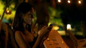 De gelukkige jonge vrouw gaat zitten als voorzitter van de het strandbar van de nachtzitkamer, glimlacht gebruikend smartphone he stock videobeelden