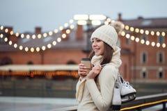 De gelukkige jonge vrouw in gebreide sweater en hoed is het gaande schaatsen stock afbeelding