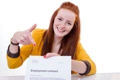 De gelukkige jonge vrouw is gelukkig over haar arbeidsovereenkomst Stock Afbeelding