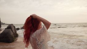 De gelukkige jonge vrouw geniet van ontspannend op de oceaan, langzame motie stock footage