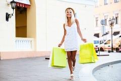 De gelukkige jonge vrouw in hoedenholding die doet terwijl het lopen winkelen in zakken Royalty-vrije Stock Afbeeldingen