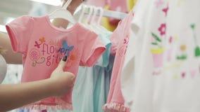 De gelukkige jonge vrouw kiest kleren voor hun kinderen Mooie vrouw in de opslag die de kwaliteit van kleren proberen stock videobeelden