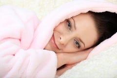 De gelukkige jonge vrouw ligt ontspannend en rustend met haar hoofd op handen Royalty-vrije Stock Fotografie