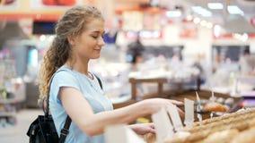 De gelukkige jonge vrouw neemt broodjes met tang in toevallige minimarket op stock videobeelden