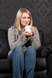 De gelukkige jonge vrouw ontspande thuis het drinken koffie Royalty-vrije Stock Afbeeldingen