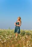 De gelukkige jonge vrouw op het gebied van camomiles. Portret in een zonnige dag Stock Foto's