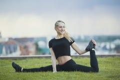 De gelukkige jonge vrouw op het gras voert streng met het gebogen been, op achtergrondcityscape uit stock foto's