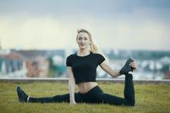 De gelukkige jonge vrouw op het gras voert streng met het gebogen been, op achtergrondcityscape uit stock foto