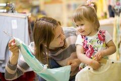 De gelukkige jonge vrouw toont haar dochter een mooie kleding Stock Afbeeldingen