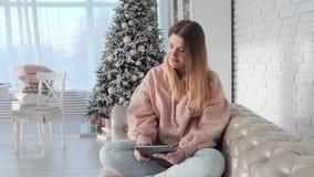 De gelukkige jonge vrouw zit op de bank en de brandingen Internet in de tablet, online betalingen, online aankopen, handigheid stock videobeelden