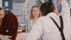 De gelukkige jonge vrouwelijke leider van het bedrijfteam viert bedrijfssucces, motiveert multi-etnisch bureauteam, dalende confe stock footage