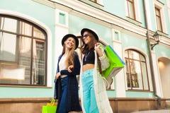 De gelukkige jonge vrouwen die en dragen zakken winkelen Royalty-vrije Stock Afbeeldingen