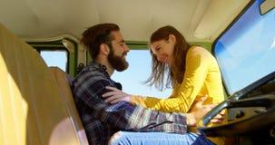 De gelukkige jonge vrouwenzitting bemant overlapping in bestelwagen op een zonnige dag 4k stock video