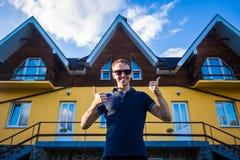 De gelukkige jonge zakenman in zonnebril kocht een groot huis voor zijn familie stock afbeelding