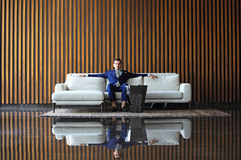 De gelukkige jonge zakenmanzitting ontspande op bank bij hotelhal gebruikend smartphon, wachtend op iemand Stock Fotografie
