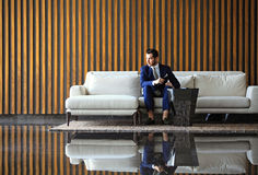De gelukkige jonge zakenmanzitting ontspande op bank bij hotelhal gebruikend smartphon, wachtend op iemand Royalty-vrije Stock Foto