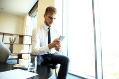 De gelukkige jonge zakenmanzitting ontspande op bank bij hotelhal gebruikend smartphone, wachtend op iemand Stock Fotografie