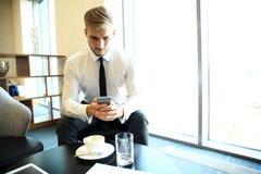 De gelukkige jonge zakenmanzitting ontspande op bank bij hotelhal gebruikend smartphone, wachtend op iemand Royalty-vrije Stock Foto