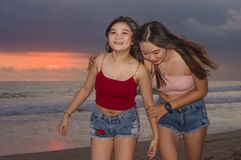 De gelukkige jonge zusters of het Aziatische Chinese meisje bij zonsondergangstrand met haar beste vriend die pret hebben die de  stock afbeeldingen