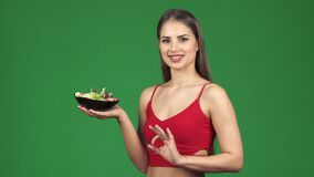 De gelukkige jongelui past vrouw die o.k. teken tonen glimlachend houdend een kom verse salade stock footage