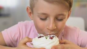 De gelukkige jongen die smakelijke roomcake, ongezonde voeding, bederfrisico eten, sluit omhoog stock footage