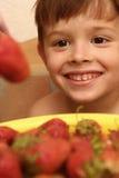 De gelukkige jongen en de rode bessen Stock Foto's