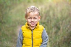 De gelukkige jongen in geel vest bekijkt de camera en het glimlachen royalty-vrije stock foto