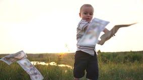 De gelukkige jongen heft geld van het gras op en werpt de dollarrekeningen in langzame motie stock videobeelden