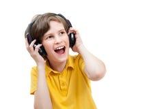 De gelukkige jongen luistert muziek met moderne hoofdtelefoons Royalty-vrije Stock Afbeelding
