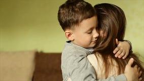 De gelukkige jongen omhelste teder zijn moeder stock videobeelden