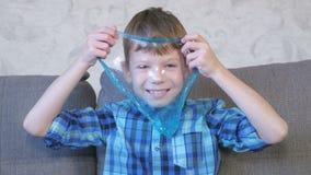 De gelukkige jongen rekt een blauwe slijmzitting op de bus en het spelen uit Het kijken door het slijm stock footage