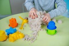 De gelukkige jongen speelt thuis kinetisch zand stock fotografie
