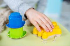 De gelukkige jongen speelt thuis kinetisch zand royalty-vrije stock fotografie