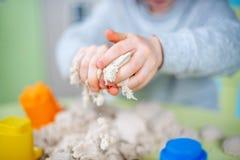 De gelukkige jongen speelt thuis kinetisch zand royalty-vrije stock foto's