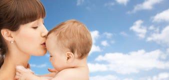 De gelukkige jongen van de moeder kussende baby over hemelachtergrond Royalty-vrije Stock Afbeelding