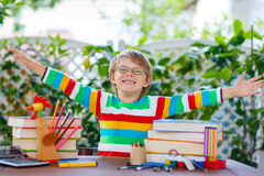 De gelukkige jongen van het schooljonge geitje met glazen en studentenmateriaal Royalty-vrije Stock Foto's