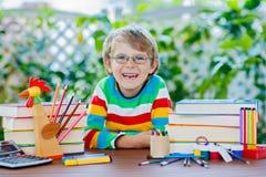 De gelukkige jongen van het schooljonge geitje met glazen en studentenmateriaal Royalty-vrije Stock Fotografie