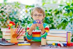 De gelukkige jongen van het schooljonge geitje met glazen en studentenmateriaal Royalty-vrije Stock Afbeeldingen